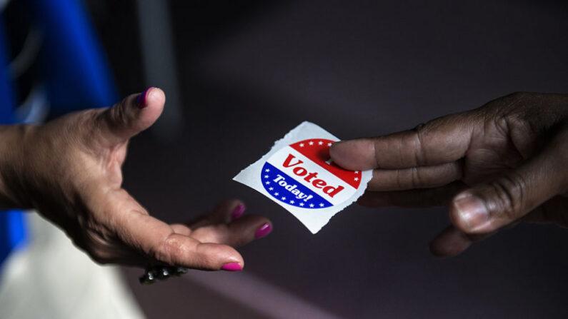 한 여론 조사원이 '난 투표했어요'라는 스티커를 나눠주고 있다. 2012년 10월 22일 촬영 | AFP=연합뉴스