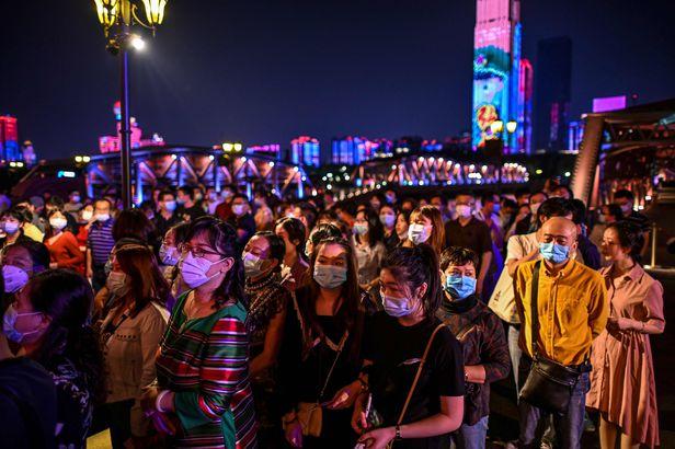 관광객들이 지난달 27일 중국 후베이성 우한의 1920년대를 재현해 놓은 드라마 세트장에서 배를 타기 위해 마스크를 쓰고 기다리고 있다.   AFP=연합뉴스