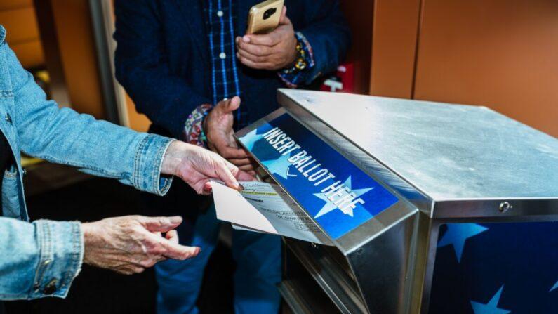 지난 10월 13일 미국 켄터키주 루이스 빌에서 유권자들이 우편투표함에 부재자 우편투표용지를 넣고 있다. | Jon Cherry/Getty Images)