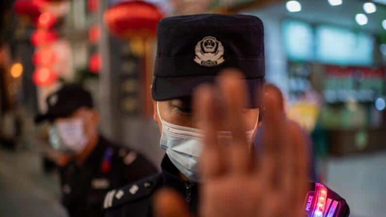 중국 베이징의 한 쇼핑몰 앞에서 마스크를 착용한 경찰이 사진 기자의 촬영을 제지하고 있다. | NICOLAS ASFOURI/AFP via Getty Images=연합
