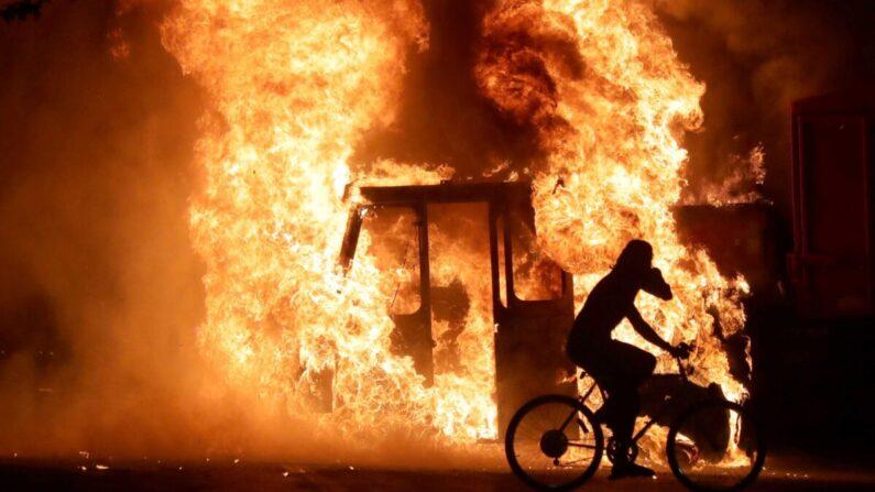 2020년 8월 23일 케노샤 폭동으로 법원 청사 앞에 세워진 차량이 불타는 가운데 한 남성이 자전거를 타고 지나고 있다.   Milwaukee Journal Sentinel via USA TODAY via REUTERS=연합뉴스