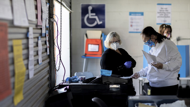 지난 3일(현지시각) 미국 조지아주 타일러스빌의 한 투표소에서 기표한 투표지를 전자투표함(스캐너)에 직접 넣는 유권자(오른쪽)를 선거 사무원이 옆에서 지켜보고 있다. | Branden Camp/AP Photo=연합