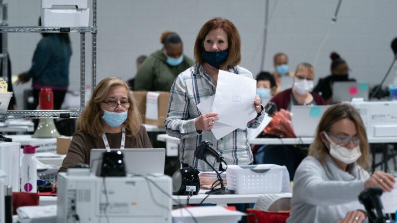7일(현지시각) 조지아주 로렌스빌의 선관위 사무소에서 선거 사무원들이 선거 감사를 위해 투표용지를 분류하고 있다. Elijah Nouvelage/Getty Images