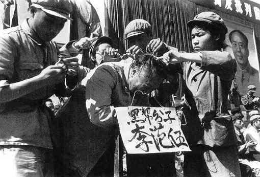 1966년 중국을 휩쓸던 문화혁명 동안 중국 공산당 간부들이 한 중국 남성을 둘러싼 채 그의 이름과 사회를 해치는 '흑색분자'라고 적힌 푯말을 목에 걸고 있다. | 퍼블릭 도메인