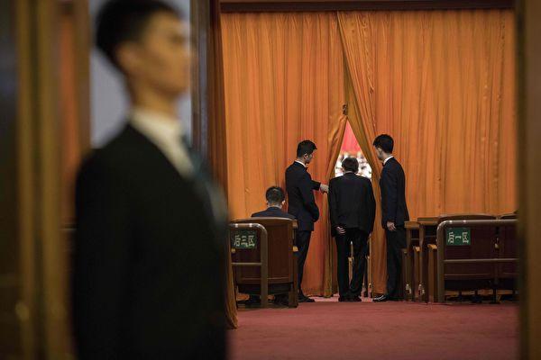 중국 양회 기간, 베이징 인민대회당에서 한 참석자가 커튼 사이를 지나 대회의장으로 입장하려 하고 있다.  NICOLAS ASFOURI/AFP/Getty Images