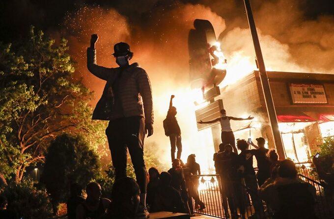 미국의 흑인 남성 조지 플로이드의 사망 사건에 분노한 시위대가 지난 5월 29일(현지시간) 새벽 미네소타주 미니애폴리스에서 방화로 불타는 한 식당 건물 앞에 모여 시위를 벌이고 있다. | 미니애폴리스=APㆍ연합