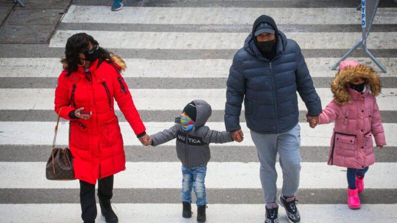 마스크를 착용한 가족이 뉴욕 타임스 스퀘어 부근 횡단보도를 지나고 있다. 2020.12.10 | KENA BETANCUR/AFP via Getty Images=연합