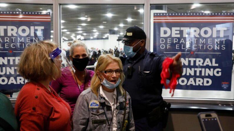 지난 11월 4일 미시간주 디트로이트시의 TCF센터에서 대선 부재자투표 개표가 진행된 가운데 경찰관이 후보 지지자들에게 손짓하고 있다. | JEFF KOWALSKY/AFP via Getty Images