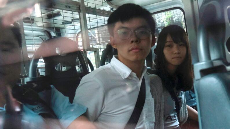 반정부 시위 혐의로 체포된 조슈아 웡과 동료 아그네스 차우가 경찰 차량을 통해 홍콩 동부법원으로 도착하고 있다. 2019년 8월 30일.   REUTERS/Tyrone Siu·연합