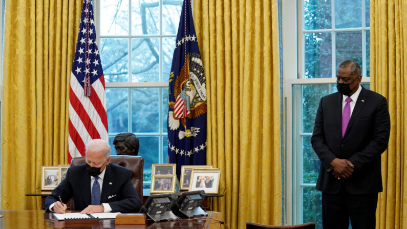 조 바이든 미국 대통령이 25일(현지시간) 워싱턴DC 백악관 내 집무실 오벌 오피스에서 로이드 오스틴 국방부 장관이 지켜보는 가운데 트랜스젠더의 군 복무를 다시 허용하는 행정명령에 서명하고 있다. | 워싱턴=로이터.연합