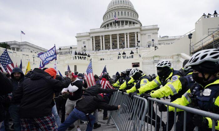 지난 6일(현지시각) 미국 워싱턴 국회의사당 부근에서 시위대와 경찰이 대치하고 있다. | AP Photo/Julio Cortez, File=연합