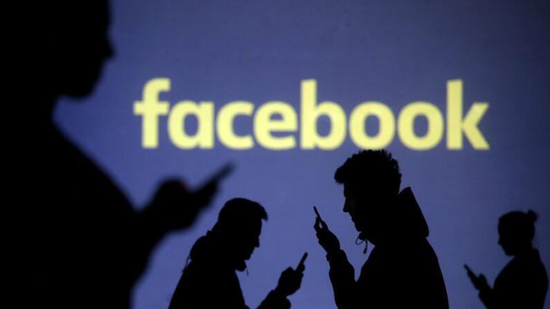 스마트폰을 든 사람들의 그림자 뒤로 페이스북 로고가 보인다.   로이터=연합