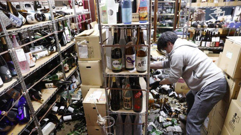 13일 지진이 발생한 후쿠시마의 한 주류 상점에서 직원이 깨진 병을 치우고 있다. | AP=연합뉴스