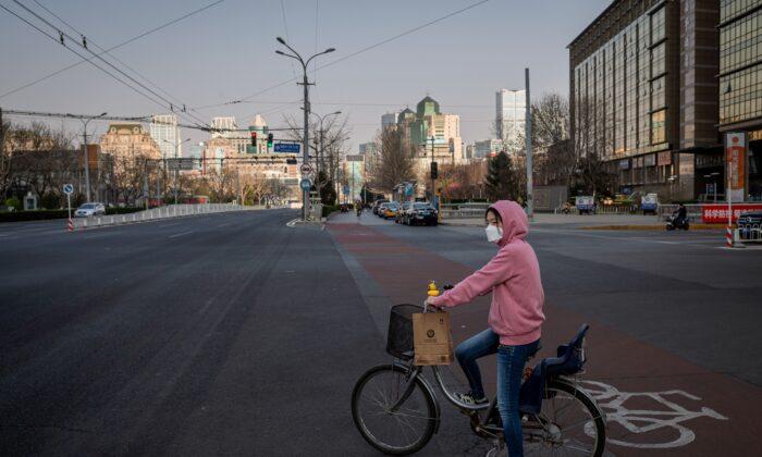 자전거를 탄 여자가 마스크를 쓴 채 베이징의 한 신호등 앞에 서있다.