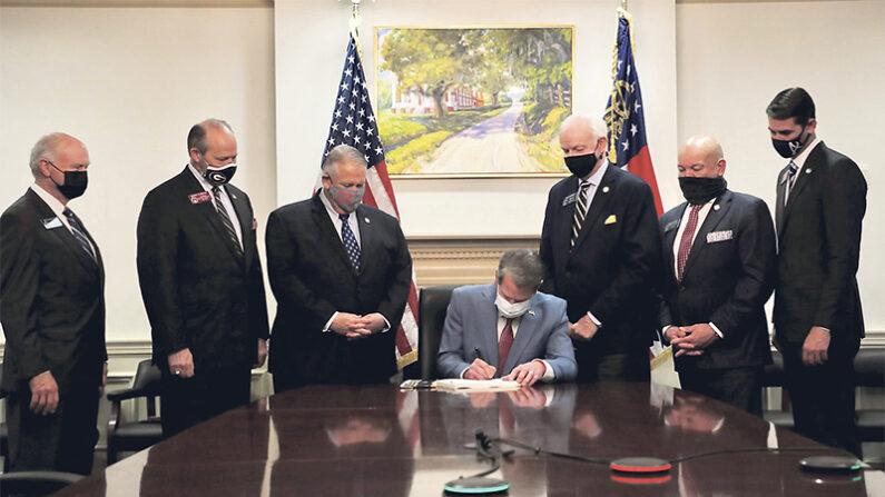 공화당 출신 브라이언 켐프 조지아 주지사가 25일 우표투표 제한을 골자로 한 선거개혁법안(SB 202)에 서명하고 있다. | 로이터 연합뉴스