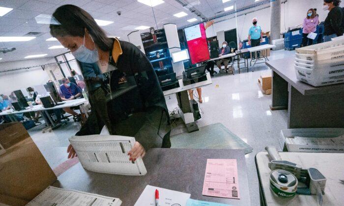 미국 애리조나주 피닉스에 마련된 마리코파 선거부(선거위원회)에서 한 사무원이 우편투표용지를 정리하고 있다. 2020.11.5 | OLIVIER  TOURON/AFP via Getty Images