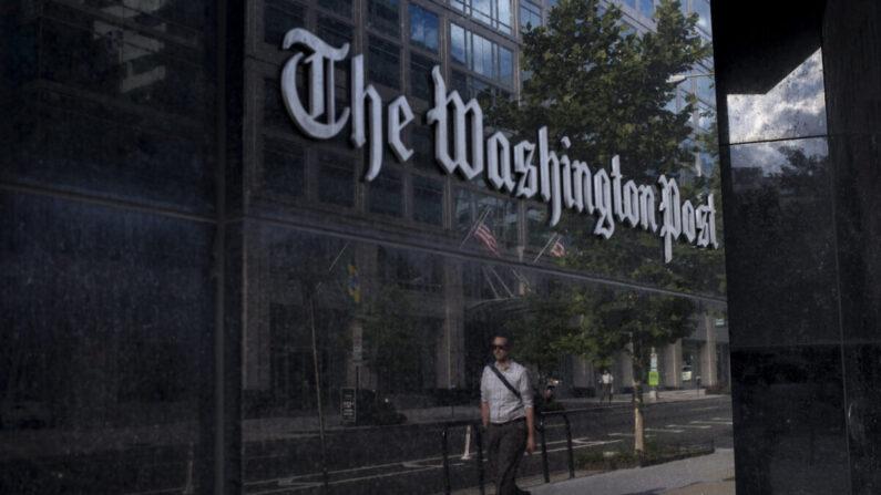 한 남성이 미국 워싱턴의 워싱턴 포스트 건물 앞을 지나고 있다.   BRENDAN SMIALOWSKI/AFP via Getty Images