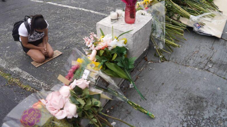 연쇄 총격 사건이 벌어진 미국 조지아주 애틀랜타의 마사지숍 '골드스파' 앞에 마련된 임시 추모소 앞에서 18일(현지시간) 한 여성이 무릎을 꿇고 희생자들을 추모하고 있다. | UPI=연합