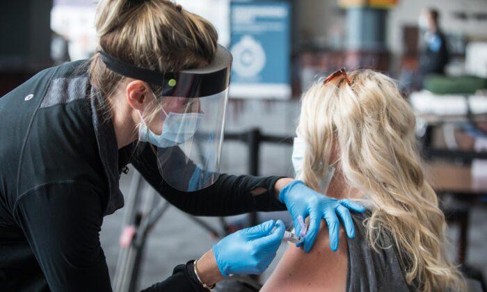 한 여성이 미국 매사추세츠주 폭스버러 질레트 스타디움에서 코로나19 백신 주사를 맞고 있다. 2021.1.15 | Scott Eisen/Getty Images