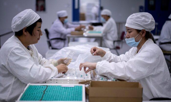 중국 북동부 랴오닝성에 있는 한 백신 개발 연구소에서 직원들이 백신을 포장하고 있다. | Noel Celis/AFP via Getty Images 연합