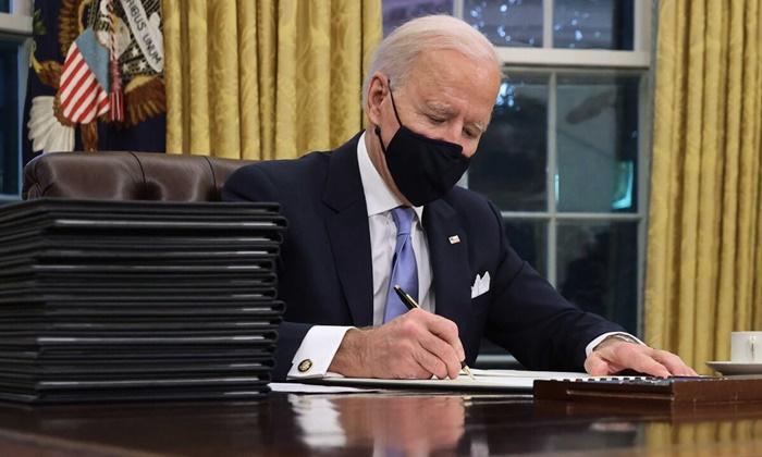 조 바이든 대통령이 1월 20일 워싱턴에서 취임한 지 불과 몇 시간 만에 백악관 집무실 리졸브 데스크에서 일련의 행정명령에 서명하고 있다.   Chip Somodevilla/Getty Images