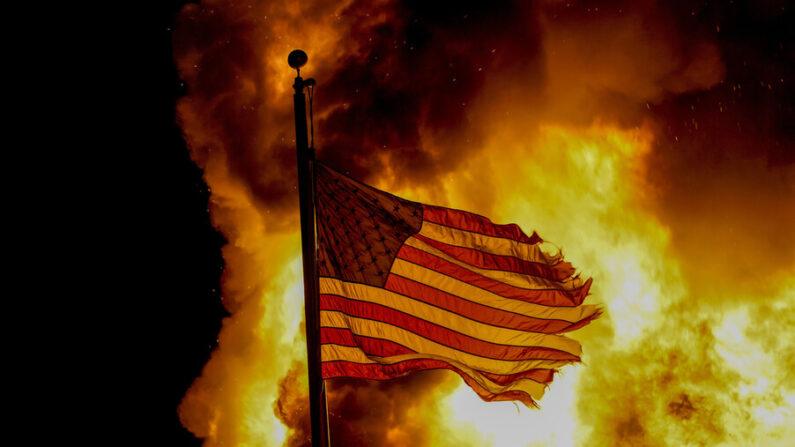 작년 5월 28일(현지시각) 지난 28일 미국 미네소타주 미니애폴리스의 불타는 건물 앞에서 흑인 남성의 죽음에 항의하는 시위자가 미국 국기를 거꾸로 들고 있다. | AP 연합뉴스