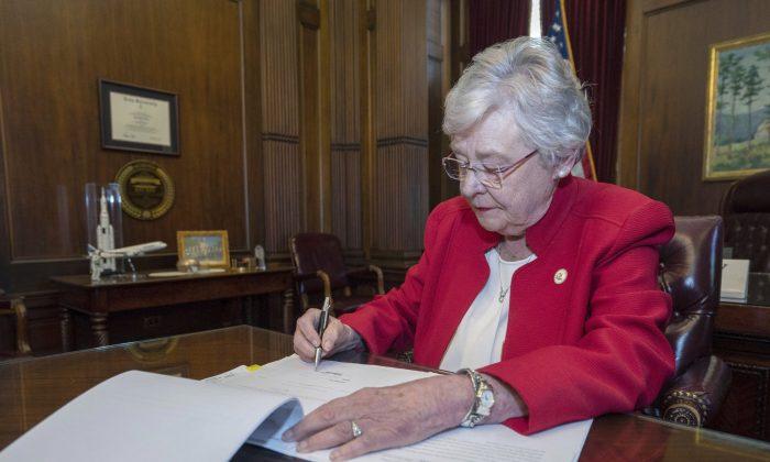 케이 아이비 앨라배마 주지사가 지난 2019년 5월 사실상 모든 낙태를 금지하는 법안에 서명하고 있다.   Hal Yeager/Alabama Governor's Office via AP 연합