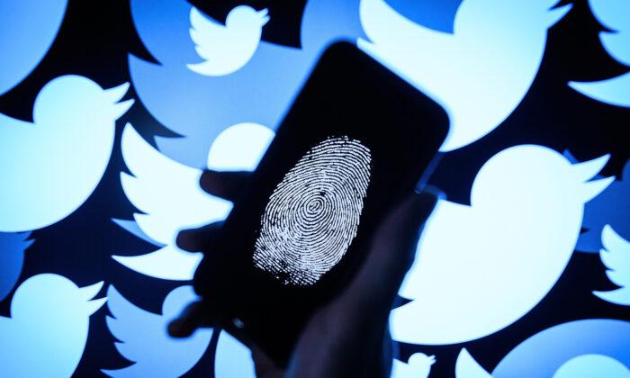 트위터 로고를 배경으로 휴대전화에 찍힌 지문이 보인다.   Leon Neal/Getty Images
