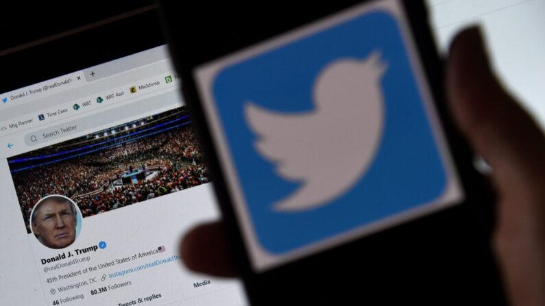 스마트폰에 트위터 로고가 표시됐다. 배경에서는 도널드 트럼프 전 대통령의 트위터 계정이 보인다. 이 사진은 트럼프 당시 대통령의 계정이 차단되기 전인 2020년 3월 촬영됐다.   OLIVIER DOULIERY/AFP via Getty Images