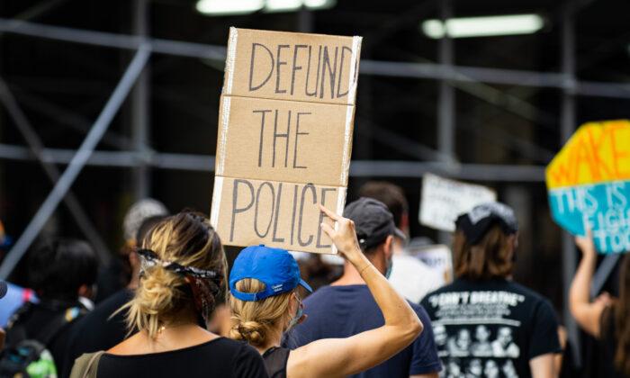 미국 뉴욕 맨해튼에서 열린 BLM 시위에서 한 시위자가 '경찰 예산 삭감' 팻말을 들고 있다.   청이호/에포크타임스