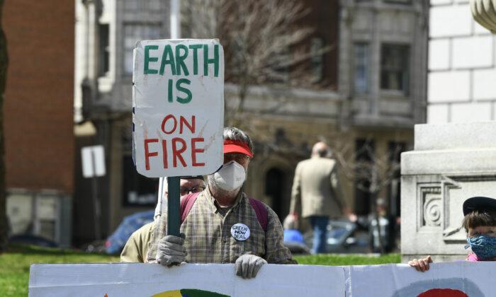 한 기후변화 활동가가 뉴욕주 알바니에서 '지구가 불났다'는 내용의 피켓을 들고 있다. 2021.4.7   Dave Kotinsky/Getty Images for Green New Deal Network