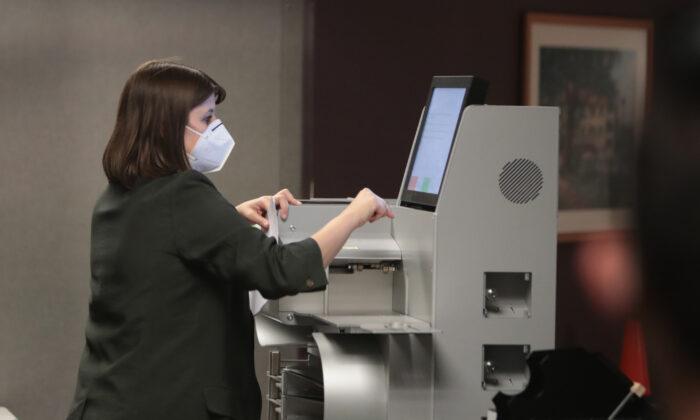 한 선거 관리 직원이 전자개표기를 통해 표를 집계하고 있다. | Photo by Scott Olson/Getty Images