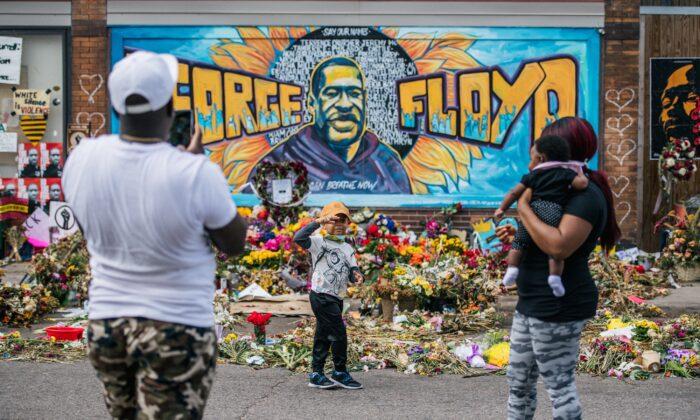 한 가족이 28일(현지시간) 미네소타주 미니애폴리스의 조지 플로이드 벽화 앞에서 사진을 찍고 있다. | Brandon Bell/Getty Images