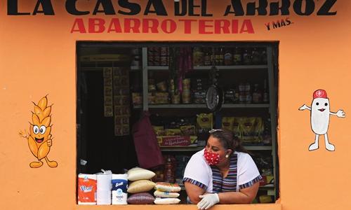 온두라스 수도 테구시갈파의 한 상점 주인이 마스크와 장갑을 착용 한 채 손님을 기자리고 있다. 2020.4.22 | ORLANDO SIERRA / AFP 연합뉴스