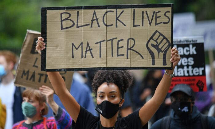 """지난해 8월 영국 런던에서 흑인 남성 조지 플로이드 사망 사건에 항의하는 시위대가 """"흑인 생명도 소중하다""""(Black Lives matter)고 적힌 피켓을 들고 있다.   Justin Tallis/AFP via Getty Images/ 연합"""