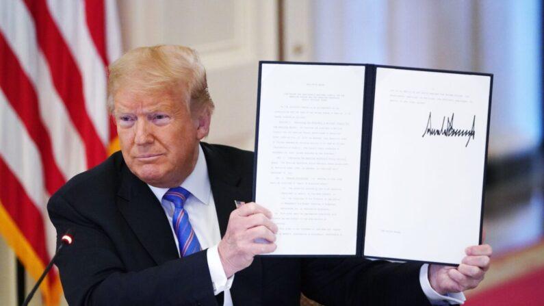 도널드 트럼프 당시 대통령이 애국교육을 위한 교육부 산하 독립기구인 '1776 위원회' 설립을 지시하는 행정명령에 서명한 뒤 들어 보이고 있다. | MANDEL NGAN/AFP via Getty Images