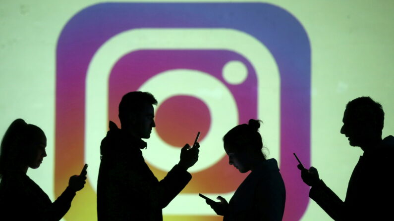 스마트폰을 든 사람들의 그림자 뒤로 인스타그램 로고가 보인다. | 로이터/연합뉴스