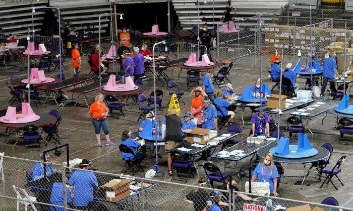 사이버 닌자스 고용자들이 미국 애리조나주 피닉스시 재향군인 기념관에서 2020년 선거 투표지를 재검표하고 있다. 2021.5.6   Matt York/AP Photo/Pool/ 연합