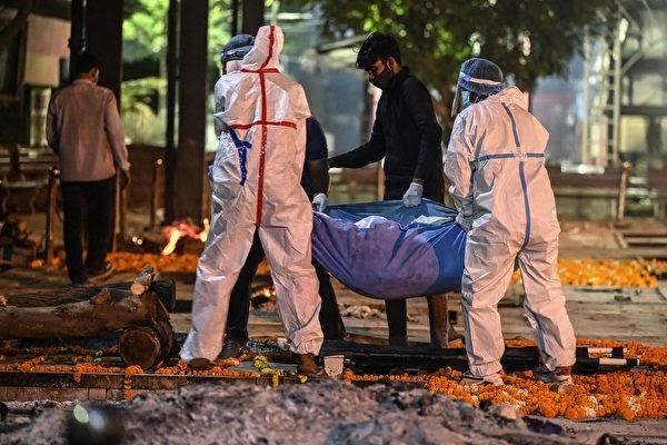 지난 4월 22일 새벽 뉴델리의 니감보드 가트(Nigambodh Ghat)의 한 화장터에서 작업자와 유족이 코로나19 사망자의 시신을 화장하기 위해 옮기고 있다. | SAJJAD HUSSAIN/AFP via Getty Images/연합