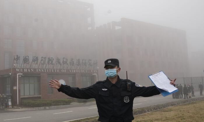 세계보건기구(WHO)팀이 현장 방문 위해 중국 후베이성 우한에 도착하자 한 보안요원이 우한 바이러스학연구소에서 기자들을 이동시키고 있다. 2021.02.03   Nog Han Guan/AP Photo/연합