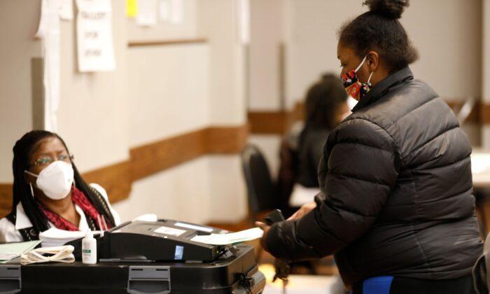 한 유권자가 2020년 총선 투표 후 투표용지를 기계에 넣고 있다. | Jeff Kowalsky/AFP via Getty Images/연합