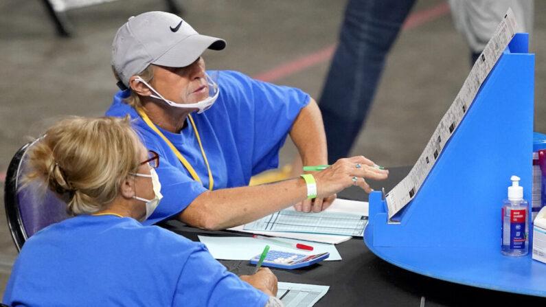 지난 5월 6일(현지시각) 애리조나주 피닉스시 재향군인 기념관에 마련된 재검표장에서 선거 감사를 진행 중인 사이버 닌자스 고용자들이 2020년 선거 투표지를 조사하고 재검표하고 있다.   Matt York/Pool/AP Photo/ 연합
