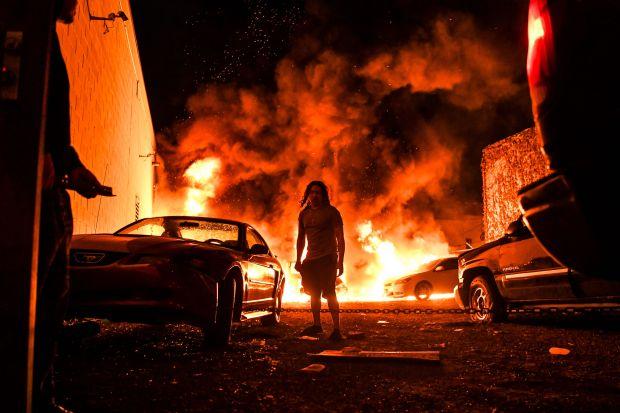 미국 미네소타주 미니애폴리스에서 조지 플로이드의 사망에 항의하는 시위가 발생해, 한 주자창이 불타고 있는 가운데 한 남성이 차량을 안전한 곳으로 옮기려 시도하고 있다. 2020.5.29 | CHANDAN KHANNA/AFP via Getty Images