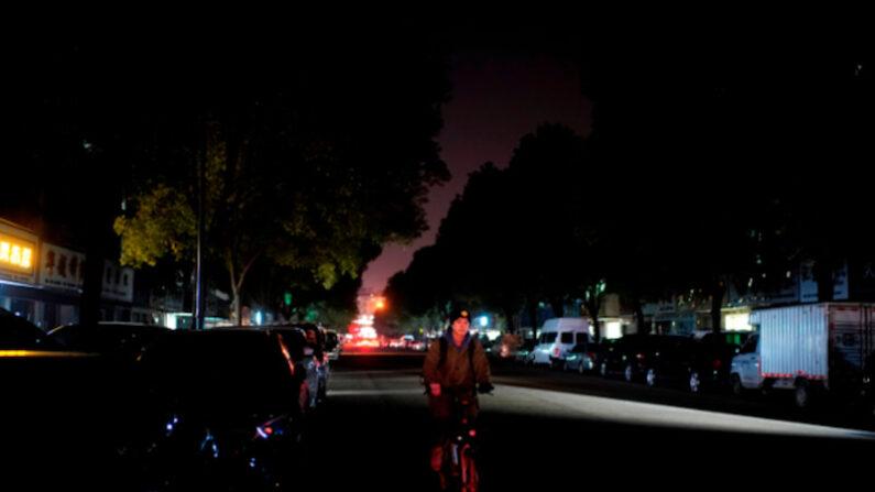중국 저장성 이우시에서 한 남성이 가로등이 꺼진 거리를 자전거를 타고 지나가고 있다. 2020.12.22 | 로이터/연합