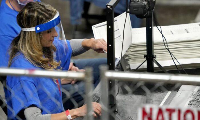 지난 6일(현지시간) 애리조나주 피닉스시에 마련된 재검표장에서 한 재검표 요원이 투표지를 개표하고 있다. | Matt York/AP Photo/ 연합