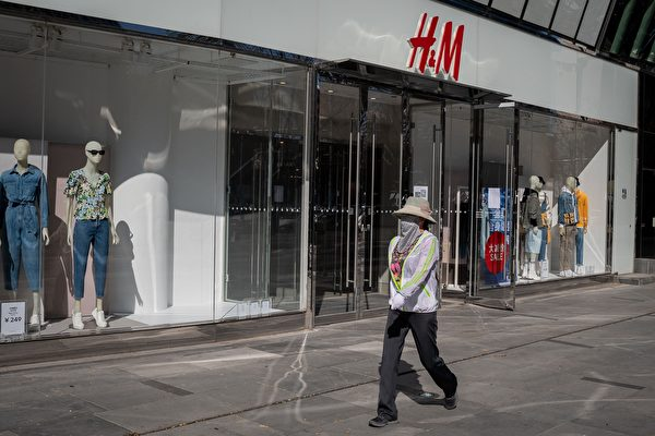 마스크를 쓴 한 여성이 2020년 3월 19일 베이징의 한 쇼핑몰에서 H&M 매점 앞을 지나가고 있다. | Photo by NICOLAS ASFOURI/AFP via Getty Images