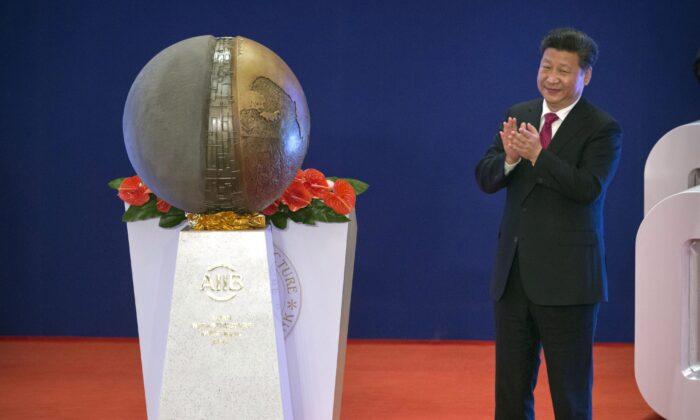 시진핑 중국 국가주석이 1월 16일 베이징에서 열린 AIIB 개막식에서 조형물을 공개한 뒤 박수를 치고 있다.   Mark Schiefelbein/Pool/AP Photo