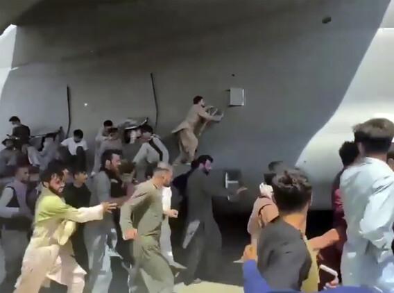 아프간을 탈출하려는 몇백명이 16일 카불 공항 활주로에서 미군 수송기 C-17을 따라 달리고 있다. 일부는 수송기에 붙어 오르려고 하고 있다.   카불=AP/연합