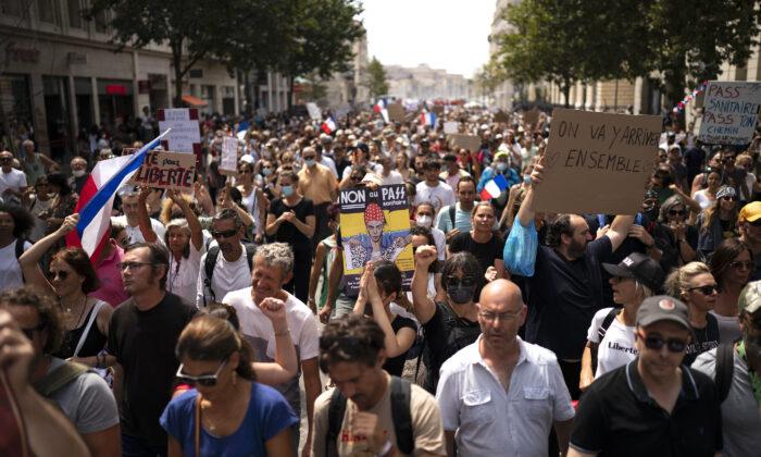 7일 프랑스 마르세유에서 코로나19 백신 접종 의무화에 반대하는 시민들이 '헬스 패스 반대' 피켓을 들고 있다. | Daniel Cole/AP Photo/ 연합