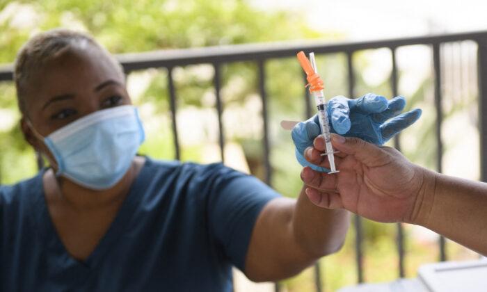 11일(현지시간) 미국 캘리포니아주의 중공 바이러스 감염증(코로나19) 백신 접종소에서 간호사가 화이자 백신을 건네받고 있다.   Patrick T. Fallon/AFP via Getty Images/ 연합
